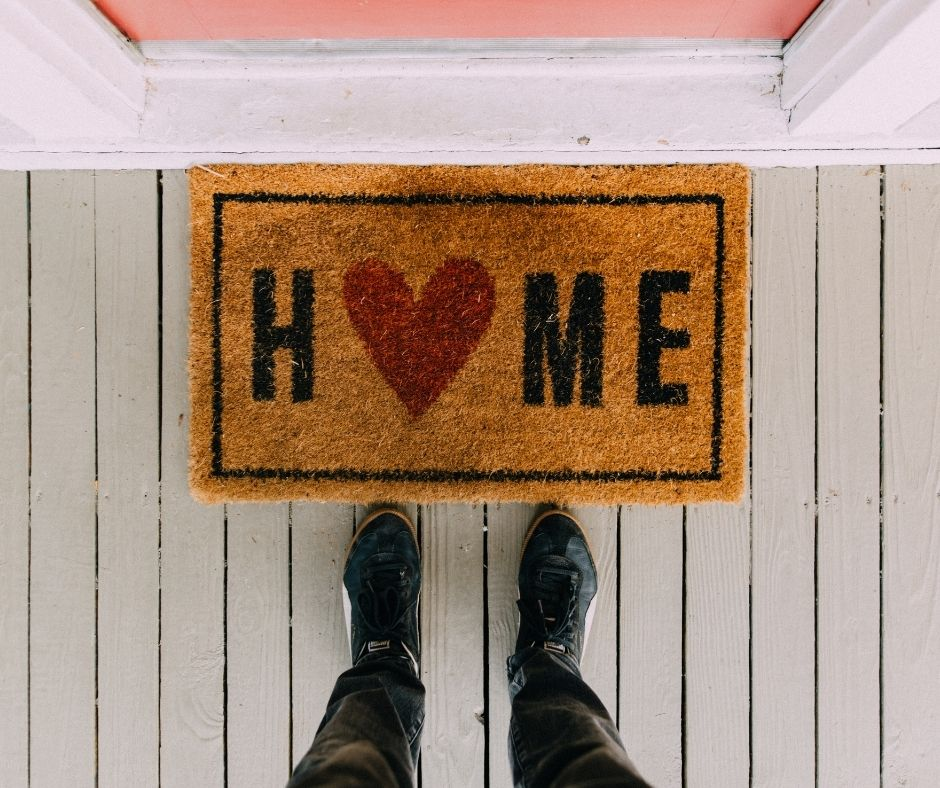 Front door mat that says home with a heart